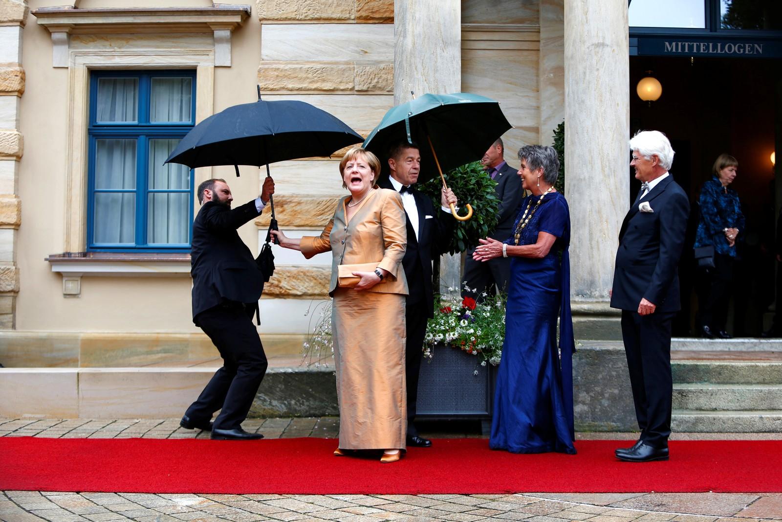 Og der kom visst regnet. Angela Merkel får en paraply før åpningen av Festspillene i Bayreuth i Tyskland.