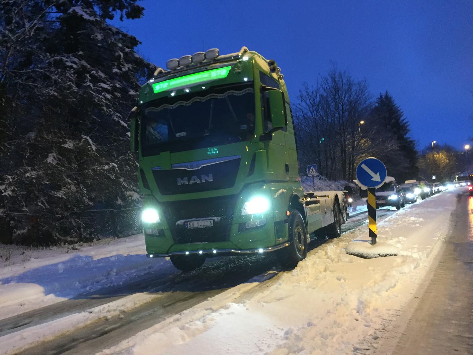 En trailersjåfør legger på kjetting i Fyllingsdalen. Køen står.