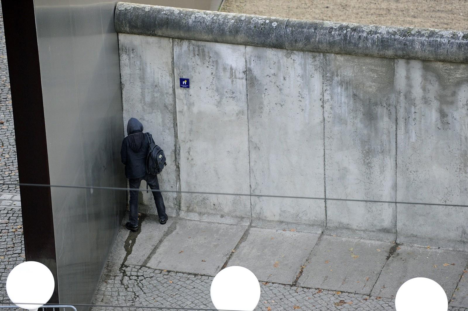 En forbipasserende markerer på sin måte på en rest av muren.