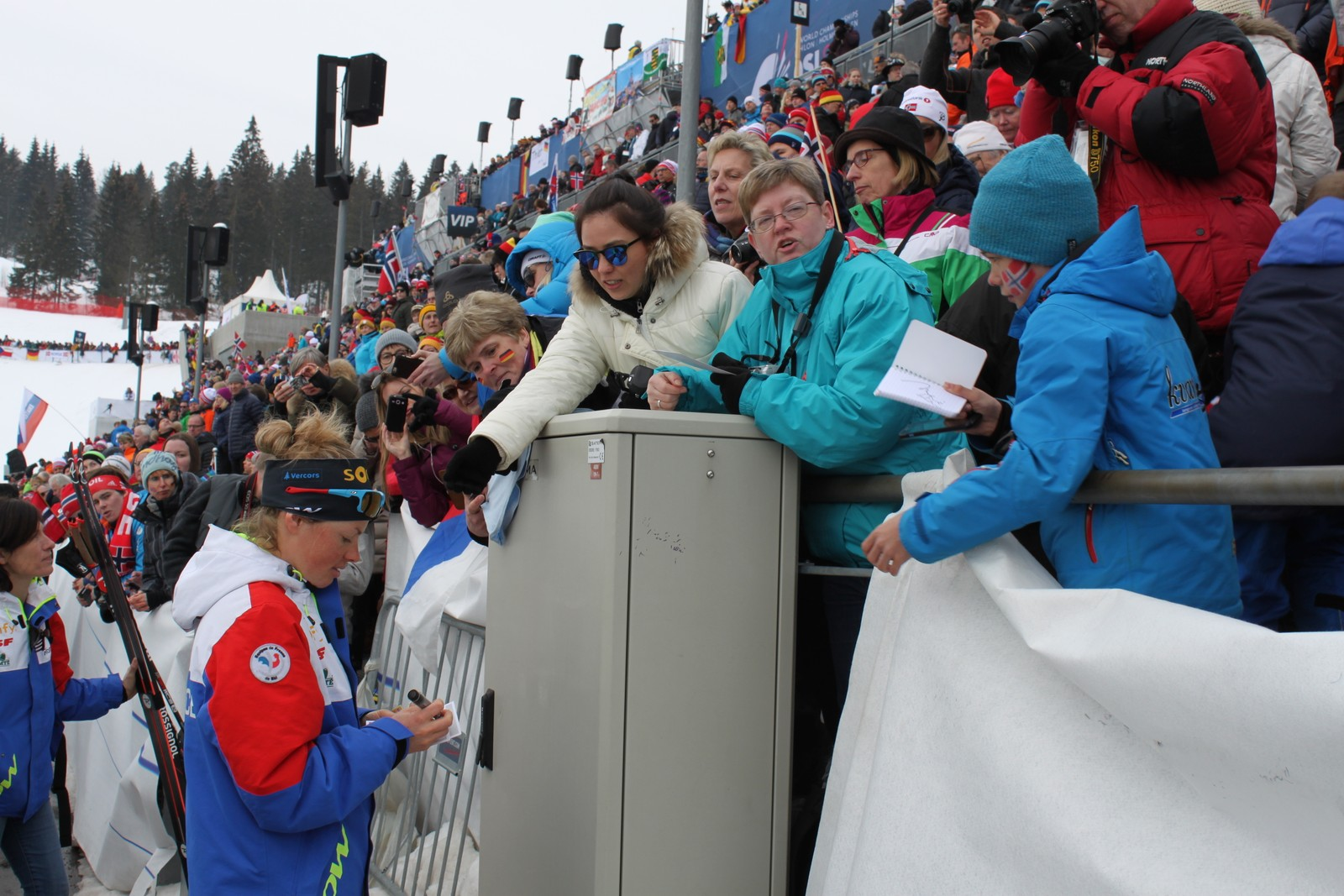 Gold medallist Marie Dorin Habert writing autographs.