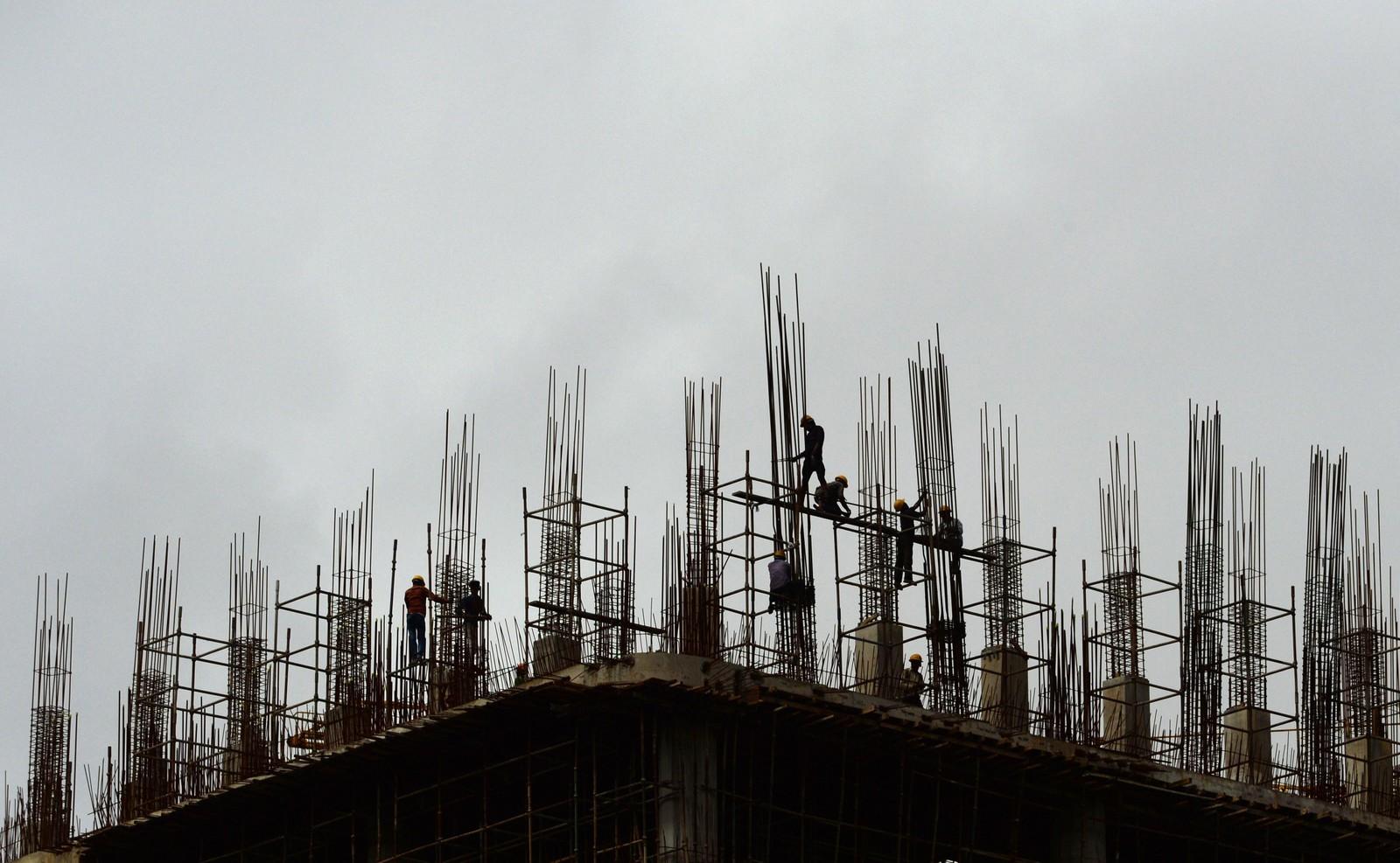 Her ser vi silhuettene av arbeidere mot monsunskyer i Mumbai i India den 4. august. De arbeider på det som skal bli en høyblokk i forretningsområdet i byen. Indias BNP vokste med 7,6 prosent i 2015 – 2016. India er landet med den hurtigst voksende økonomien i verden.
