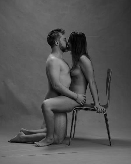 En naken dame med mørkt hår sitter på en stol og kysser en naken mann med mørkt hår og skjegg som står på kne mellom bena henne sog holder henne på rumpa