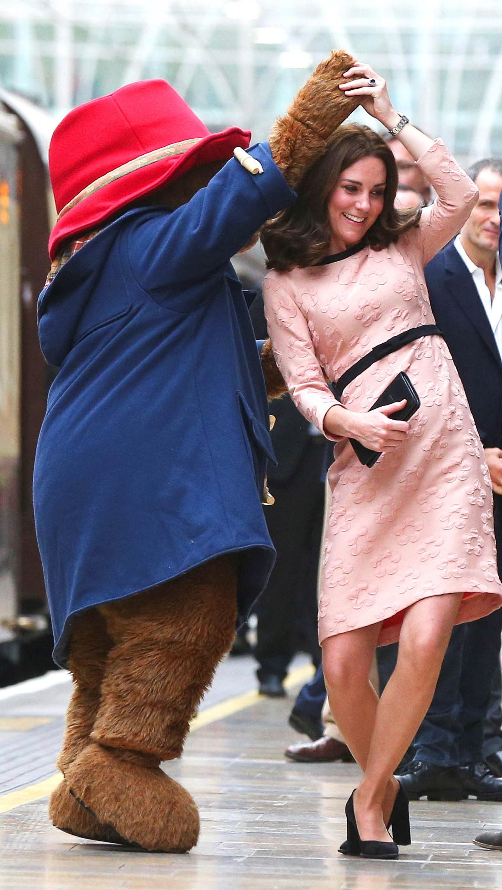 Hertuginne Catherine og Paddington danser på Paddington Station i London.