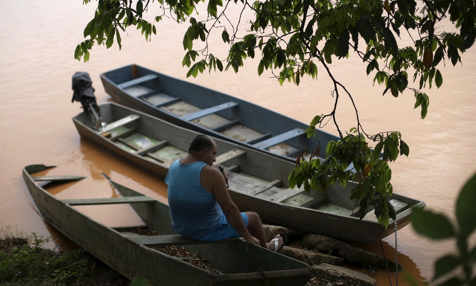 Ein mann sit ved elva som vart fylt med gjørme etter at to demningar brast for to veker sidan.