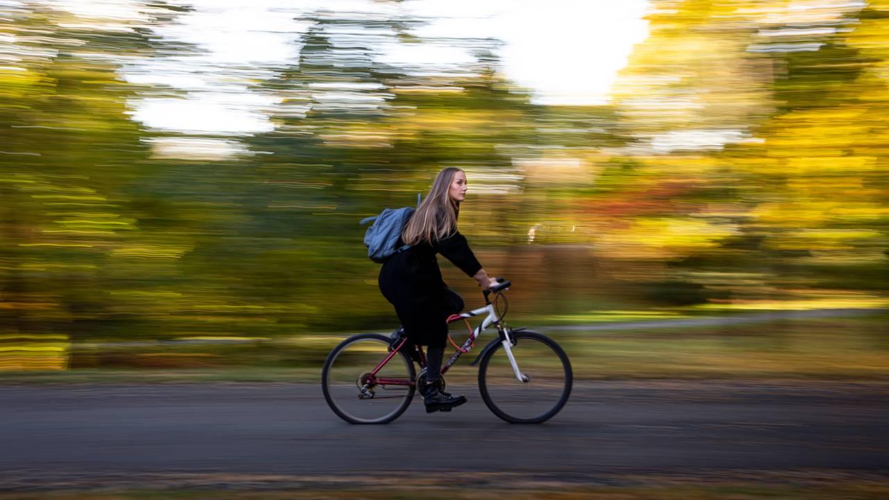 Ingvild Dagsland sitter på en gammel sykkel på en asfaltert vei. Bildet er tatt i fart, så bakgrunnen er uklar, men høstfargene på trærne skinner gjennom. Hun har på kåpe og sekk på ryggen.