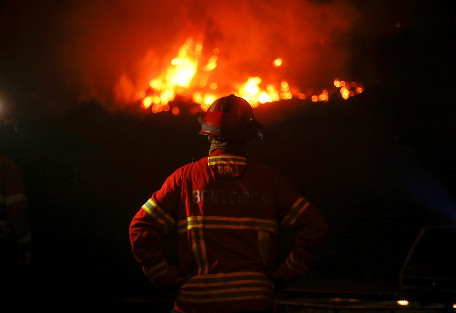 Brannmannen ser på flammene 19. juni.