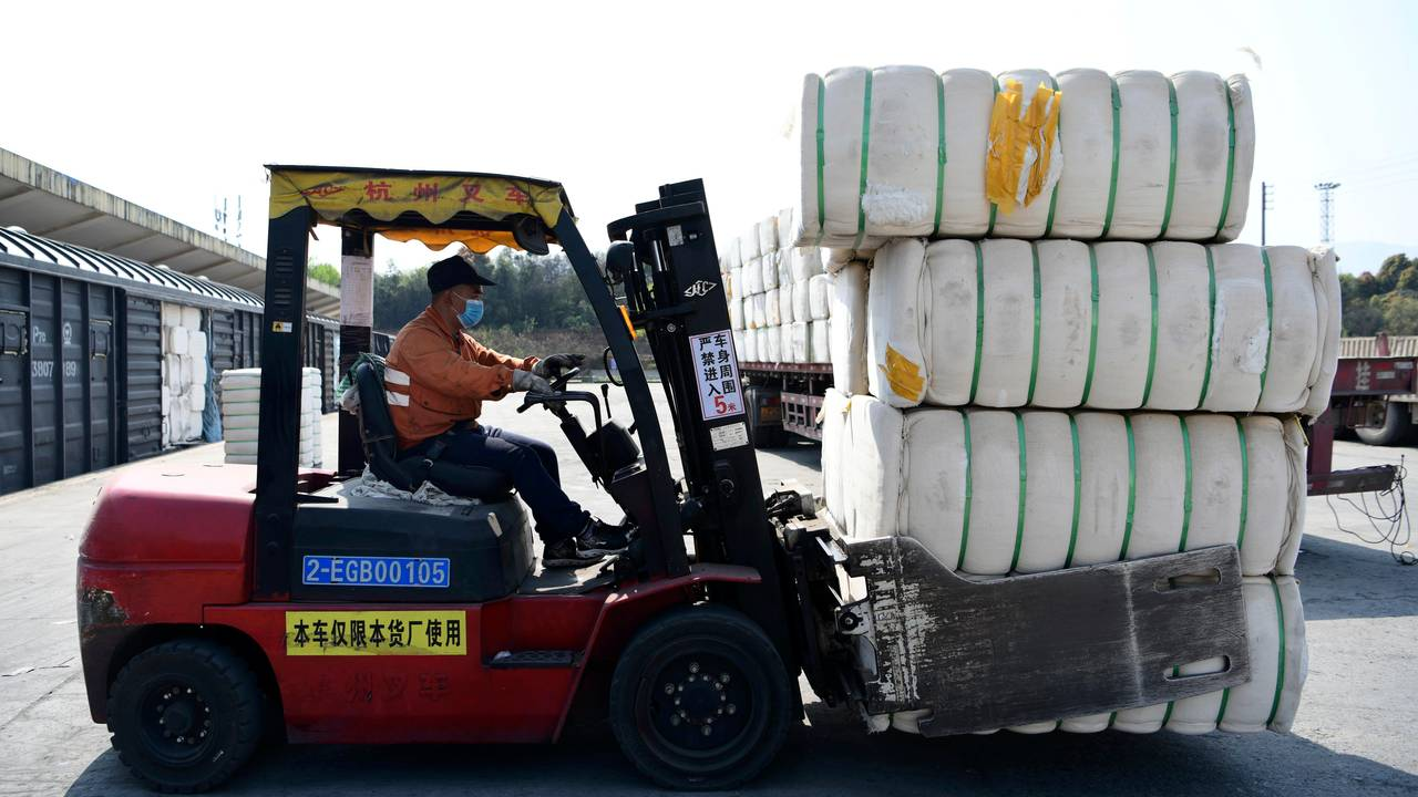 En arbeider flytter på store pakker med bomull fra Xinjiang. ved en godsterminal i Jiujiang i Jiangxi-provinsen Bildet er tatt 26. mars 2021.