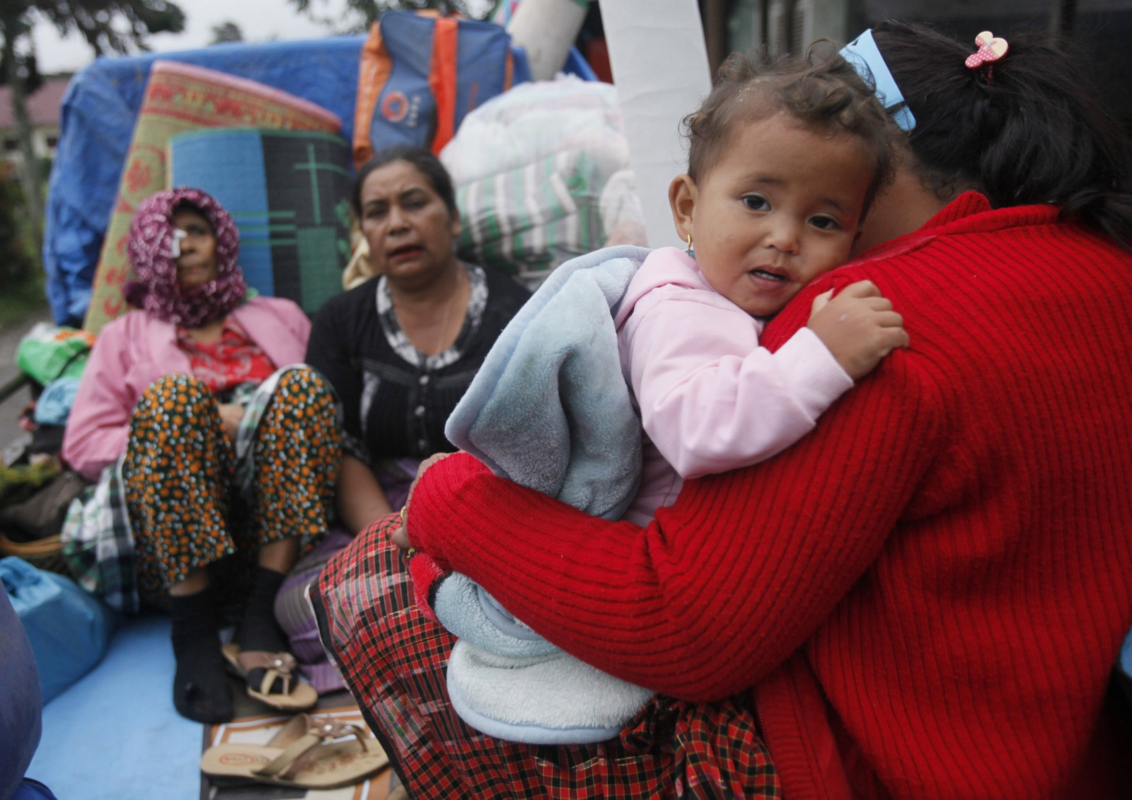 Kvinner og barn blir evakuert bort fra vulkanasken.