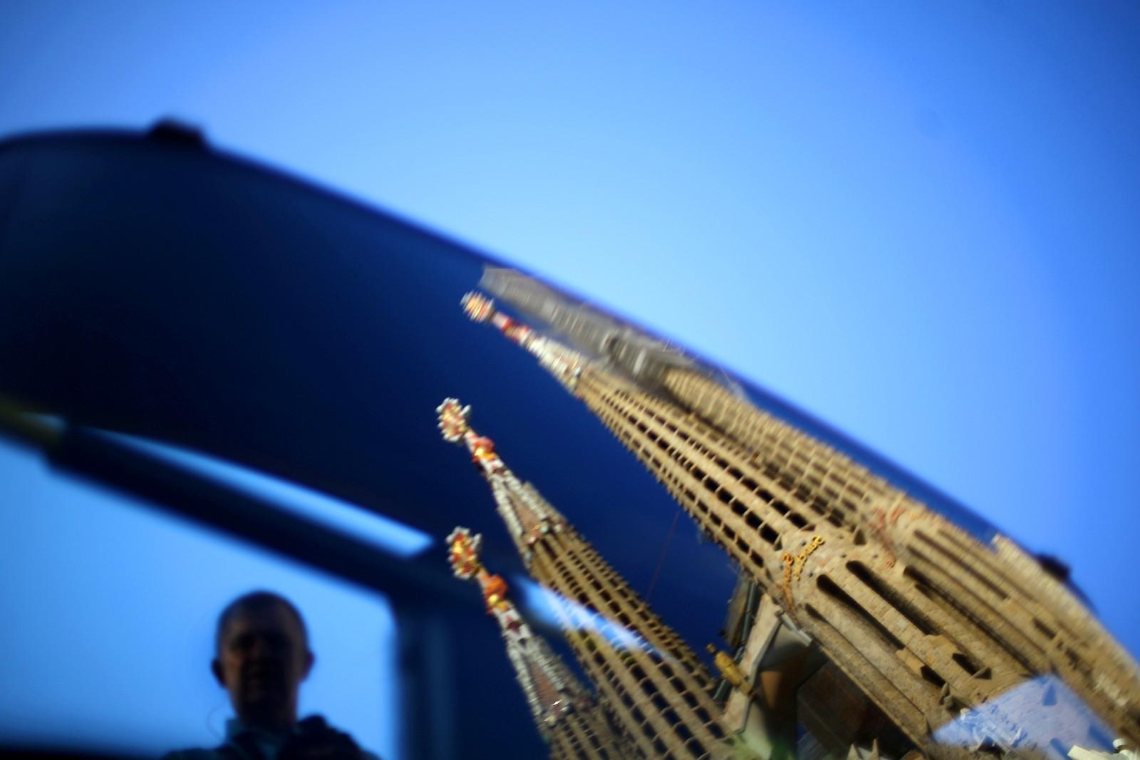 Et speilbilde av Sagrada Familia i et bussvindu i Barcelona.