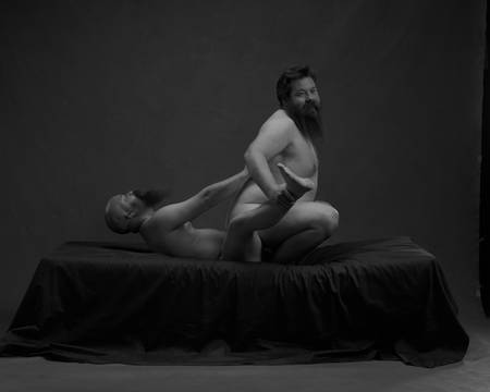 En skallet mann med skjegg ligger på ryggen og sprer beina. En kraftig bygd mann med skjegg sitter med ryggen mot ham, mellom beina til den andre og smiler mot kamera. Begge er nakne, men ingen kjønnsorganer er synlige.