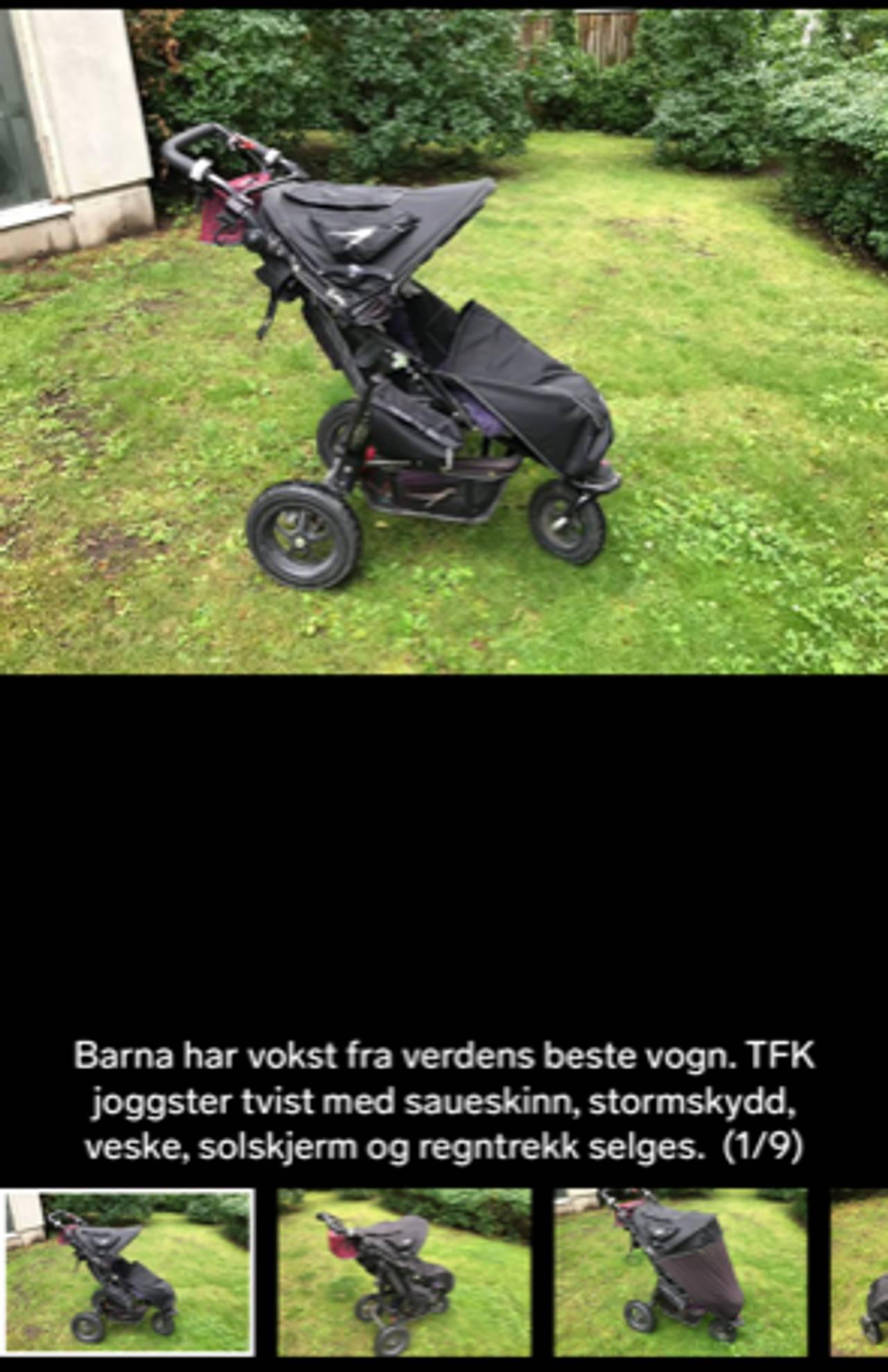 Sort barnevogn på grønt gress