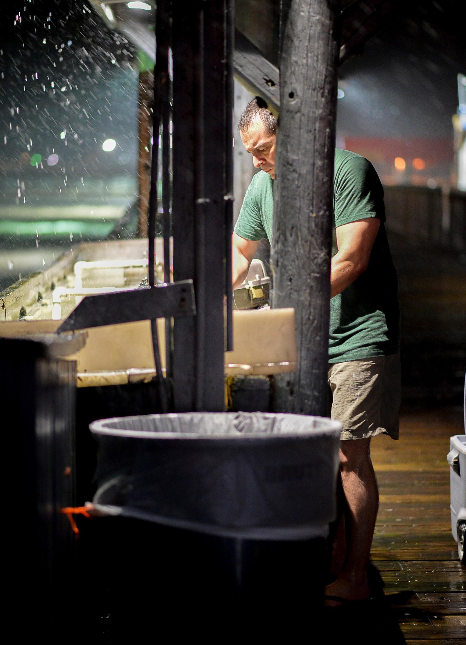 Steve Vega vasker dagens fangst på fiskebrygga i Port Isabel mens vinden er i ferd med å ta seg opp.