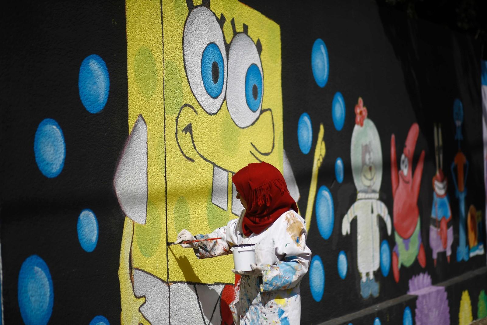 En palestinsk kunstner maler barne-TV-figuren Svampebob på veggen til en skole drevet av FN (UNRWA) i Gaza by.