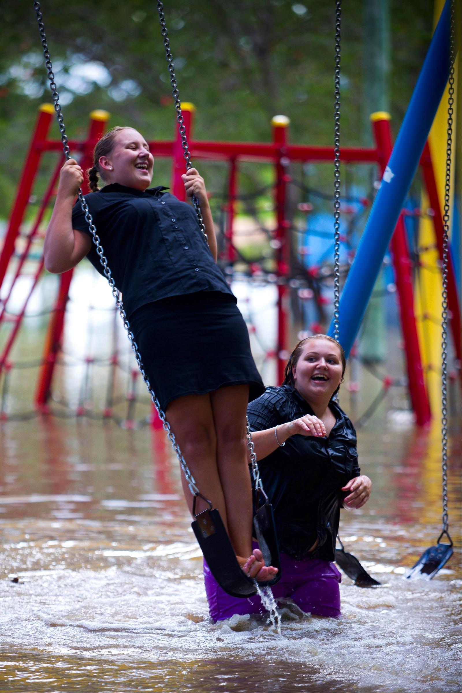 Crystal Warner og Sharnia Johns leker i flomvannet i Beenleigh i Australia.