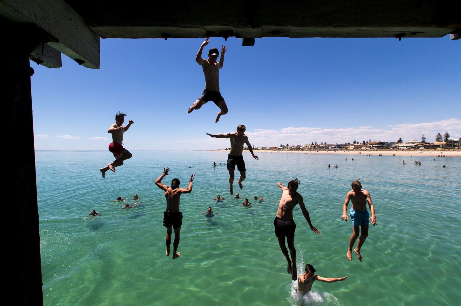 I Australia koser de seg på stranda før jul. Her ved Henley beach i Adelaide, der det ble registrert 42,9 grader denne uka.