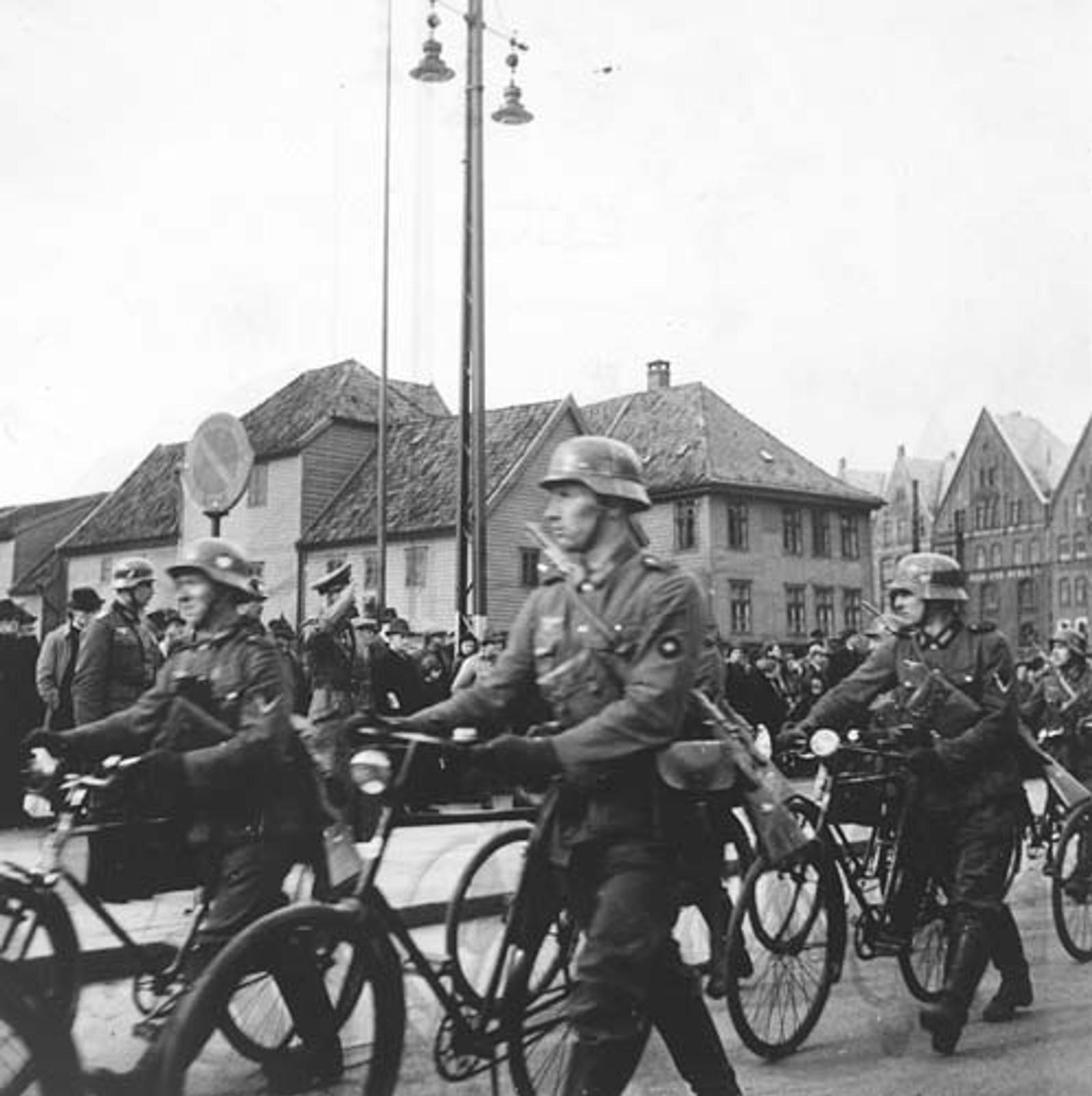 MARSJERER: Tyske soldater utstyrt med sykler marsjerer over Fisketorget.