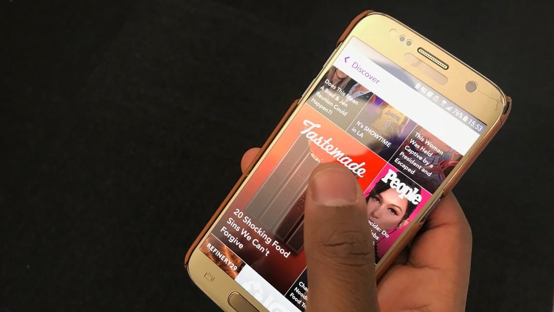 En brun hånd holder en smarttelefon med snapchat på