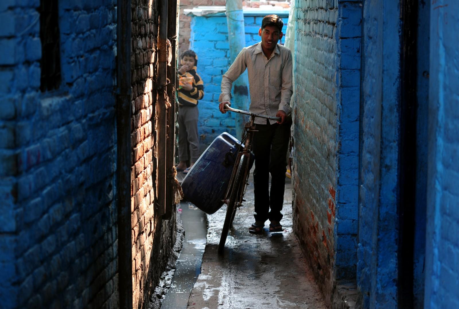 En gutt i New Delhi frakter en vanntank på sykkelen sin.