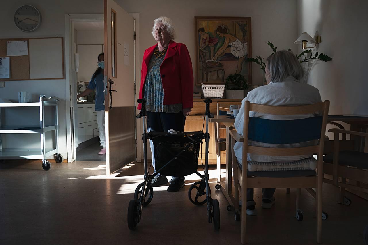 Anne Marie står rakrygget opp ved siden av frokostbordet i sin røde jakke