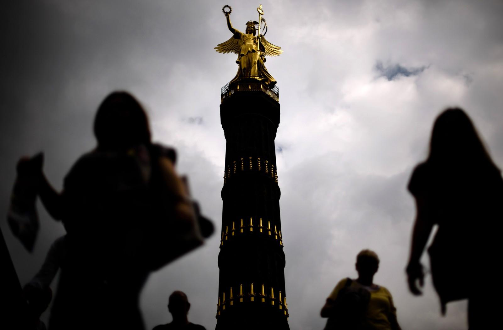 Mennesker går forbi den berømte Seierssøylen i Berlin i Tyskland. Statuen forestiller den romerske seiersgudinnen Victoria, og ble oppført mellom 1864 og 1873. Bildet er tatt den 5. august.