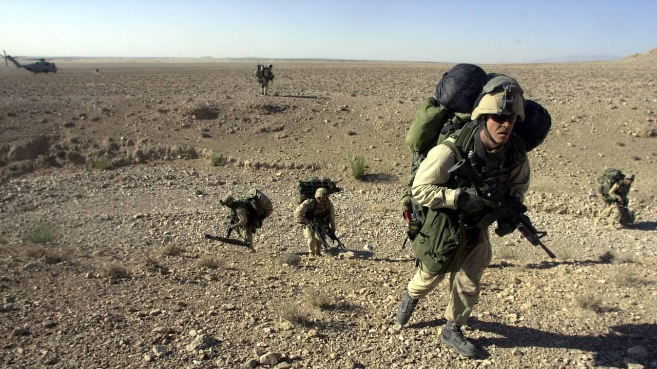 Amerikanske marineinfanterister på jakt etter Al Qaida og deres gjemmesteder. Bildet er tatt etter at de ble sluppet av fra et helikopter utenfor Kandahar i Sør-Afghanistan 10. desember 2001.