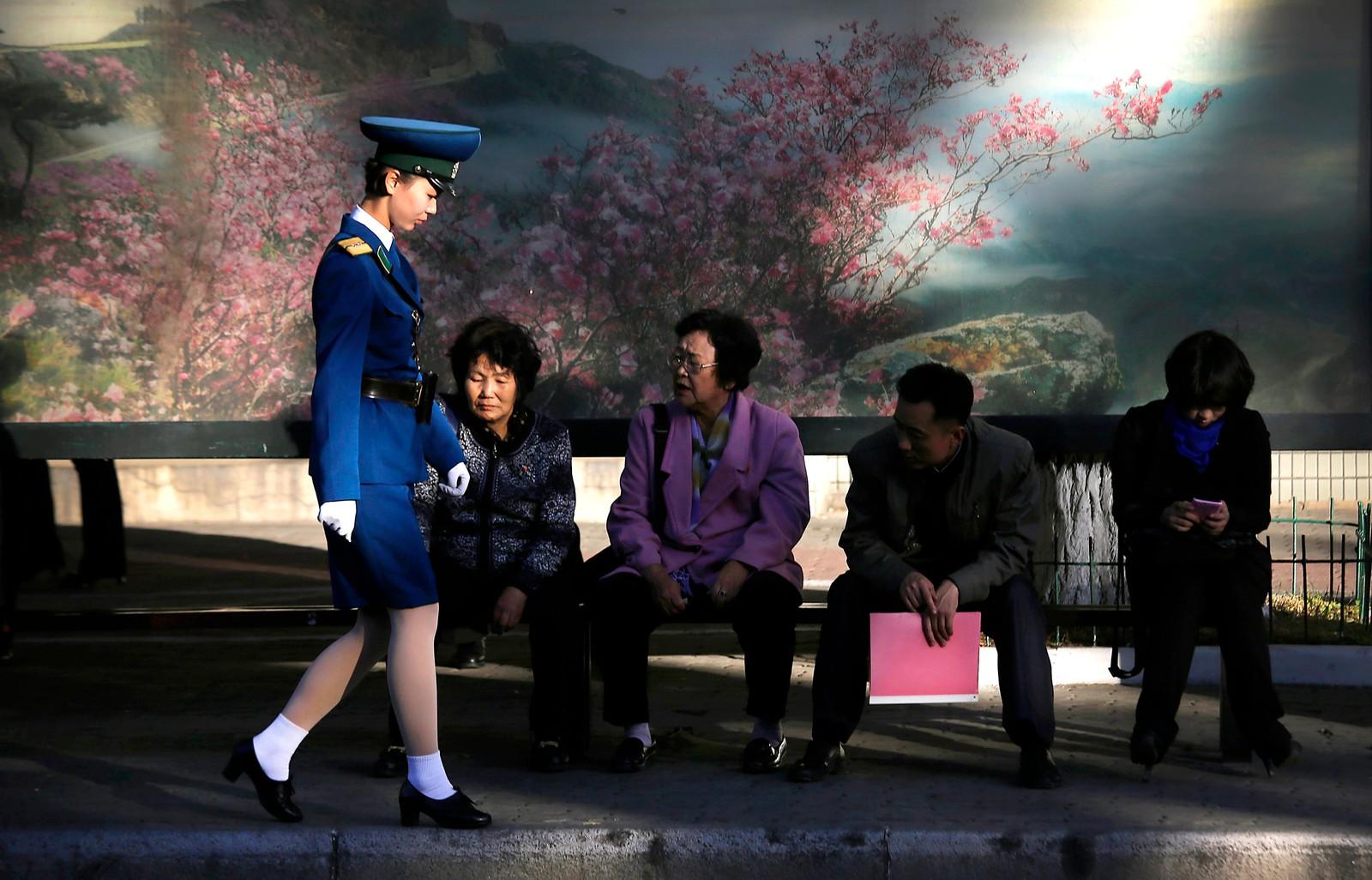 En nordkoreansk politikvinne går forbi en buss-stopp i Pyongyang.