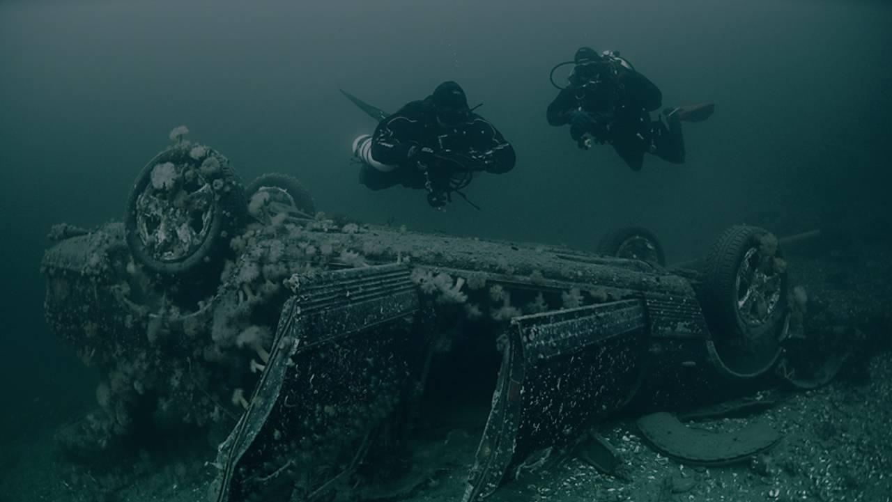 Dykkere ser på en Mercedes liggende opp ned på havbunnen.