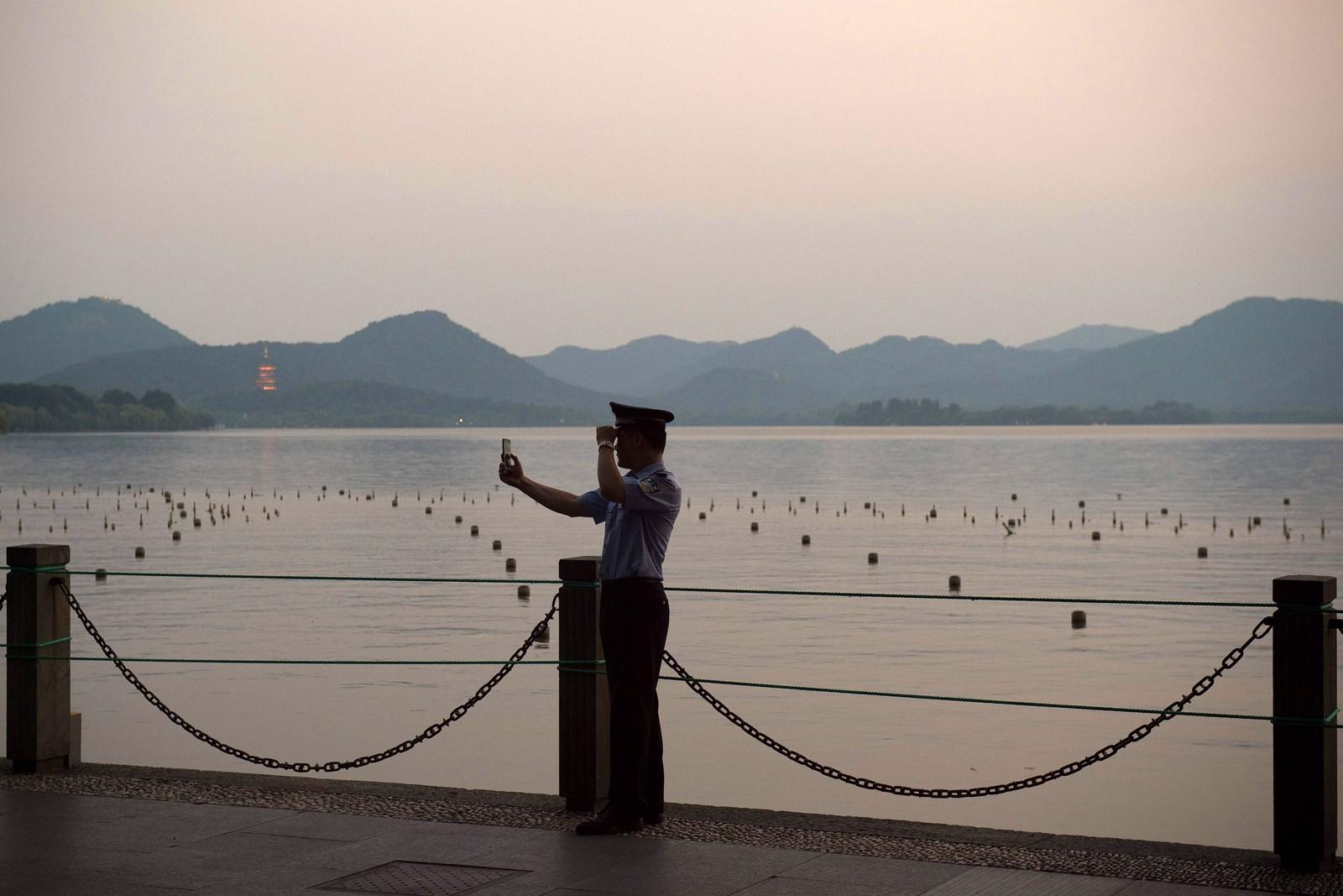 En politimann tar en selfie mens han overvåker et område i Hangzhou i Kina den 2. september. Fabrikker er stengt for at man skal kunne se en blå himmel, potensielle bråkmakere er stengt inne, og befolkningen skal ha blitt oppfordret til å ta knekken på plagsomme fluer, kakerlakker, gnagere og mygg. Alt dette for at byen skal ta seg godt ut når verdensledere fra de største økonomiene skal delta på G20-toppmøtet.