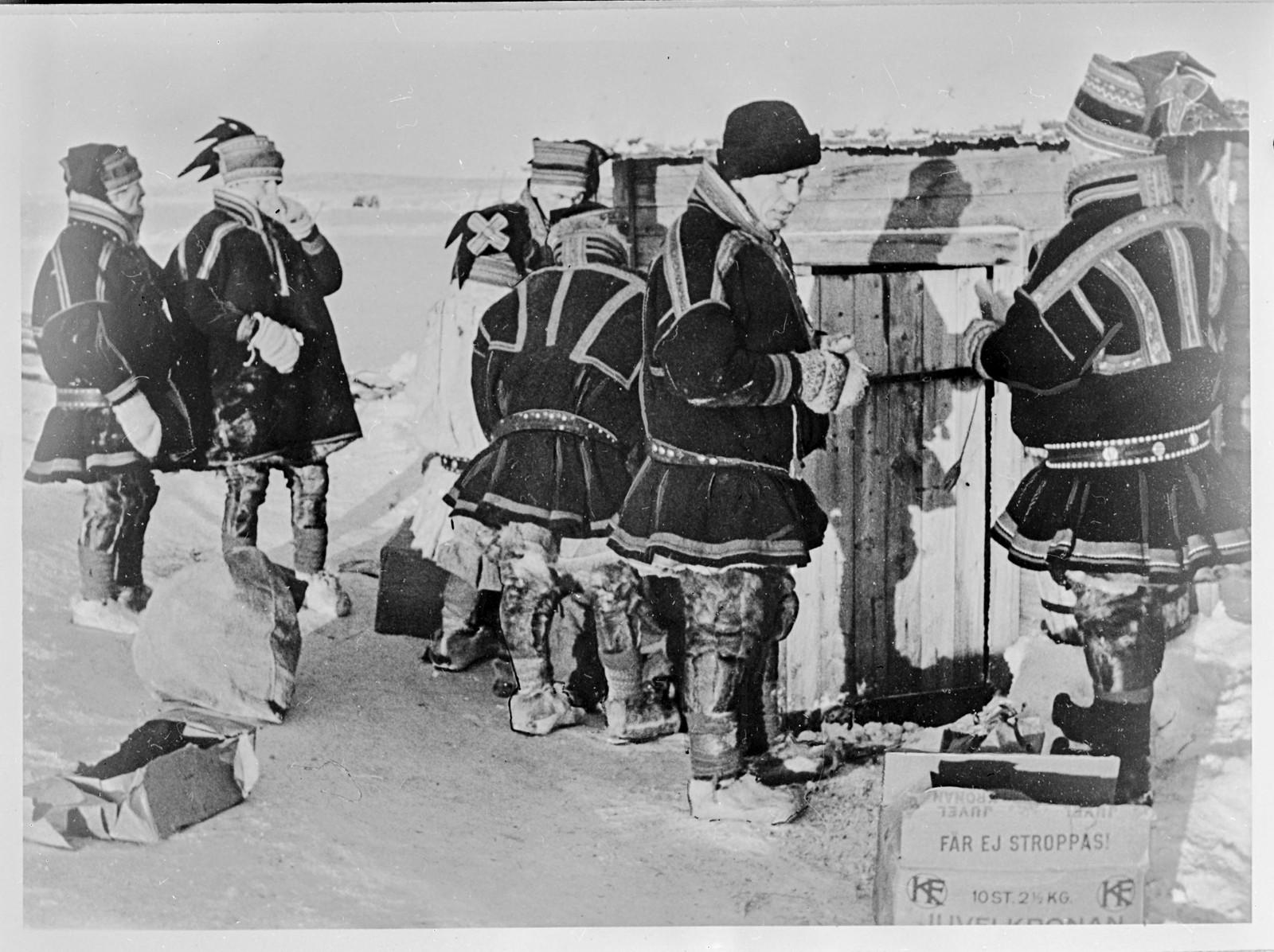 """Original bildetekst:"""" Vinteren 1944 gjennomførte tyskerne tvangsevakuering av sivilbefolkningen i Finnmark og brente deres bosteder. Det lyktes en god del av folket å flykte innover fjellet, hvor de imidlertid støtte på de største vanskeligheter. Fra svensk side er det igangsatt en effektiv hjelpevirksomhet hvoved store mengder klær og matvarer er distribuert til befolkningen. Bildet viser: Nordmenn i karakteristiske lappeklær venter på at boden hvor de etterlengtede matvarer oppbevares skal åpnes. Stockholm 12.2.45."""""""