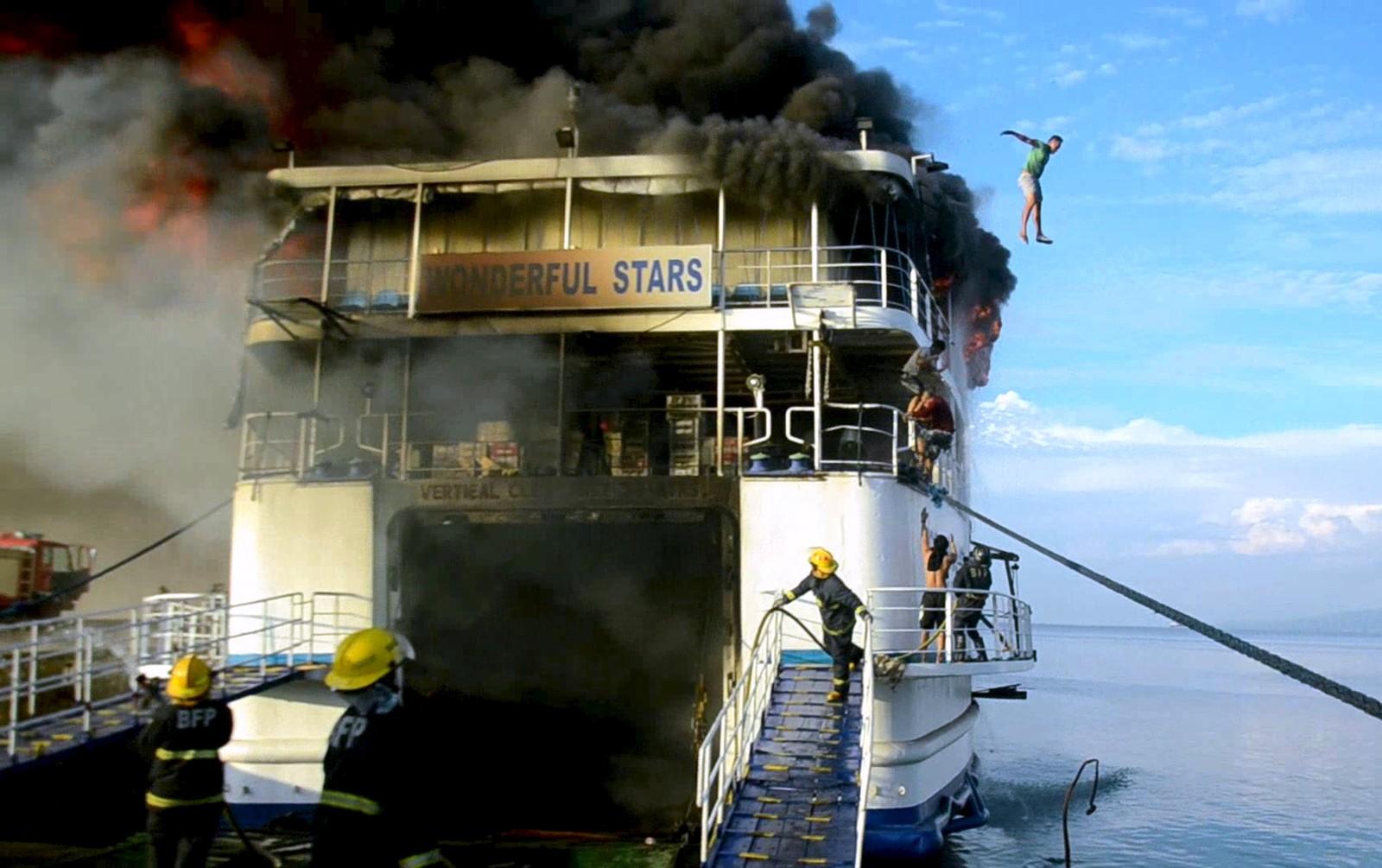 Et medlem av mannskapet fra MV Wonderful Stars hopper ut av det brennende skipet ved havna i Ormoc, Fillippinene 15. august. De 544 passasjerene ble trygt evakuert, mens tre av mannskapet på skipet ble skadd.