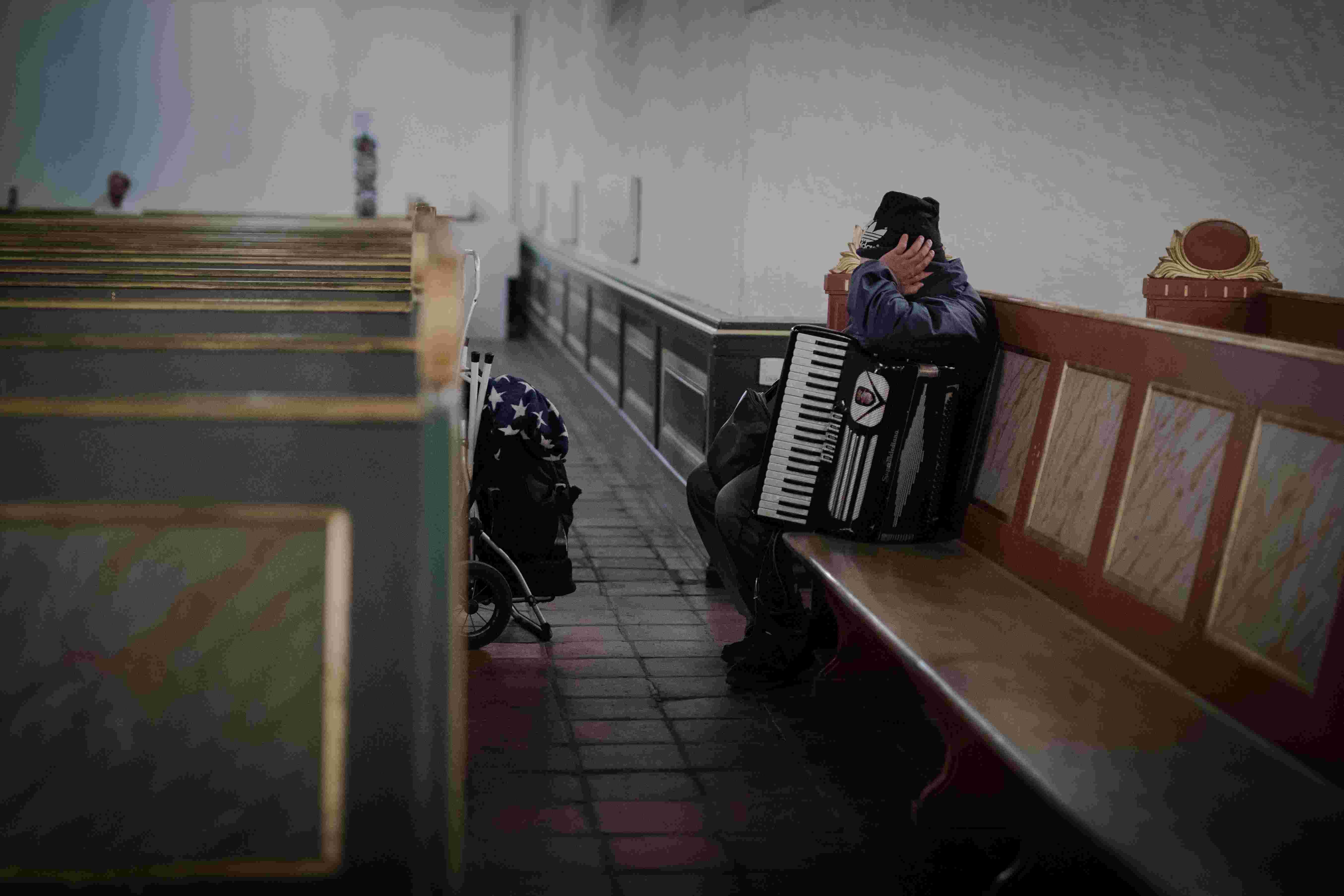 Mann med trekkspill hviler på kirkebenk