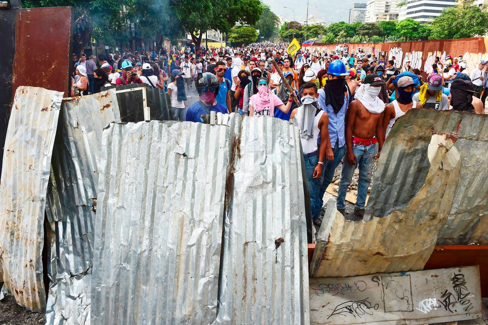 Demonstrantene river ned gjerder for å lage barrikader i byen.