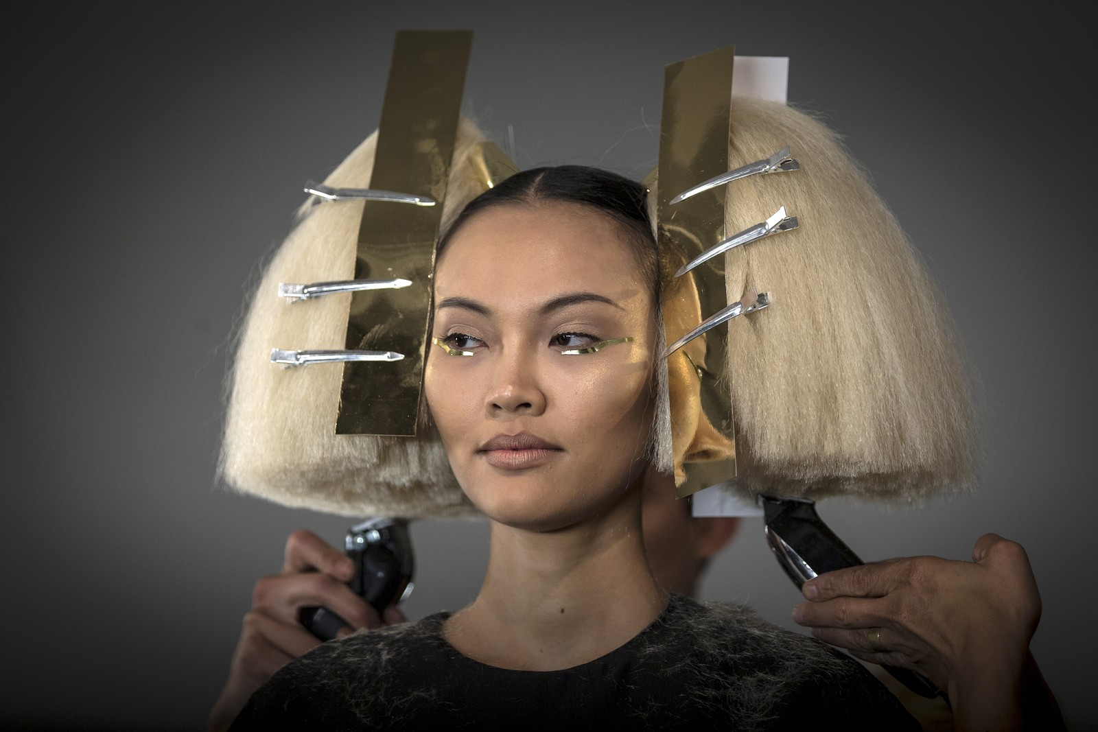 En modell får siste finpuss på hårsveisen før hun skal ut på catwalken under moteuka i New York.