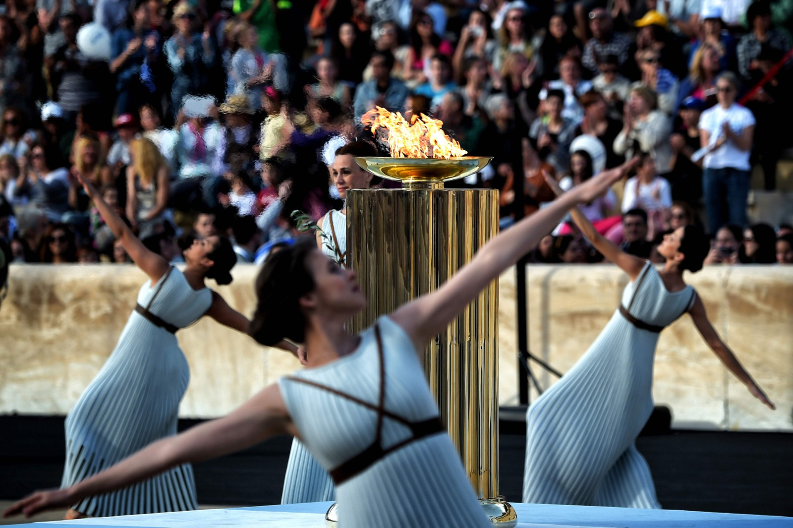 Prestinner danser rundt OL-flammen under overleverings-seremonien på Panatinean stadion i Aten onsdag denne uken, da OL-ilden offisielt ble overrakt representanter fra sommer-OL i Rio de Janeiro. Overrekkelsen markerte at det var 100 dager til OL starter 5. august.