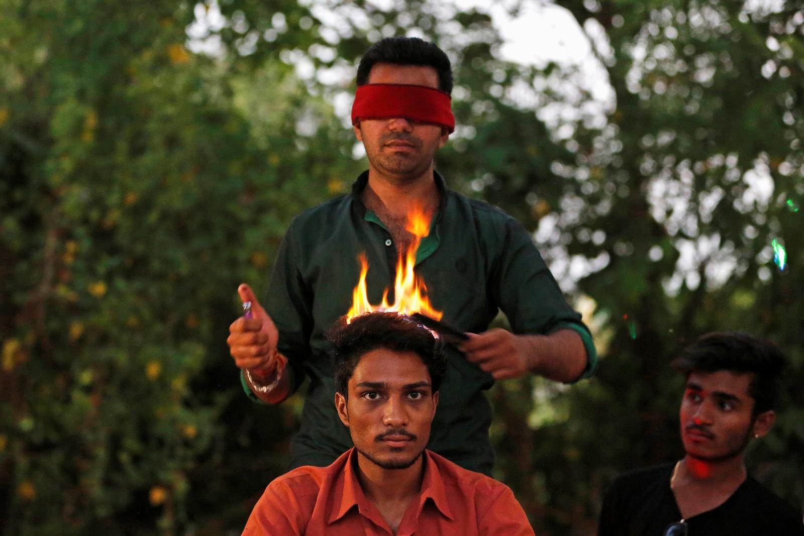 """En frisør med bind for øynene og åpen ild er nok en lite fristende kombinasjon for de fleste. Den indiske """"hårkunstneren"""" Vishnu Limbachiya tilbyr imidlertid akkurat det i en park i Ahmedabad."""