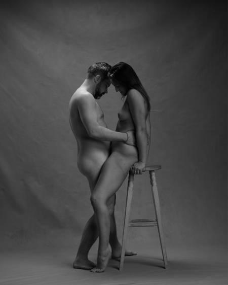 En naken mann står mellom bena på en naken kvinne som hviler rumpa på en høy krakk