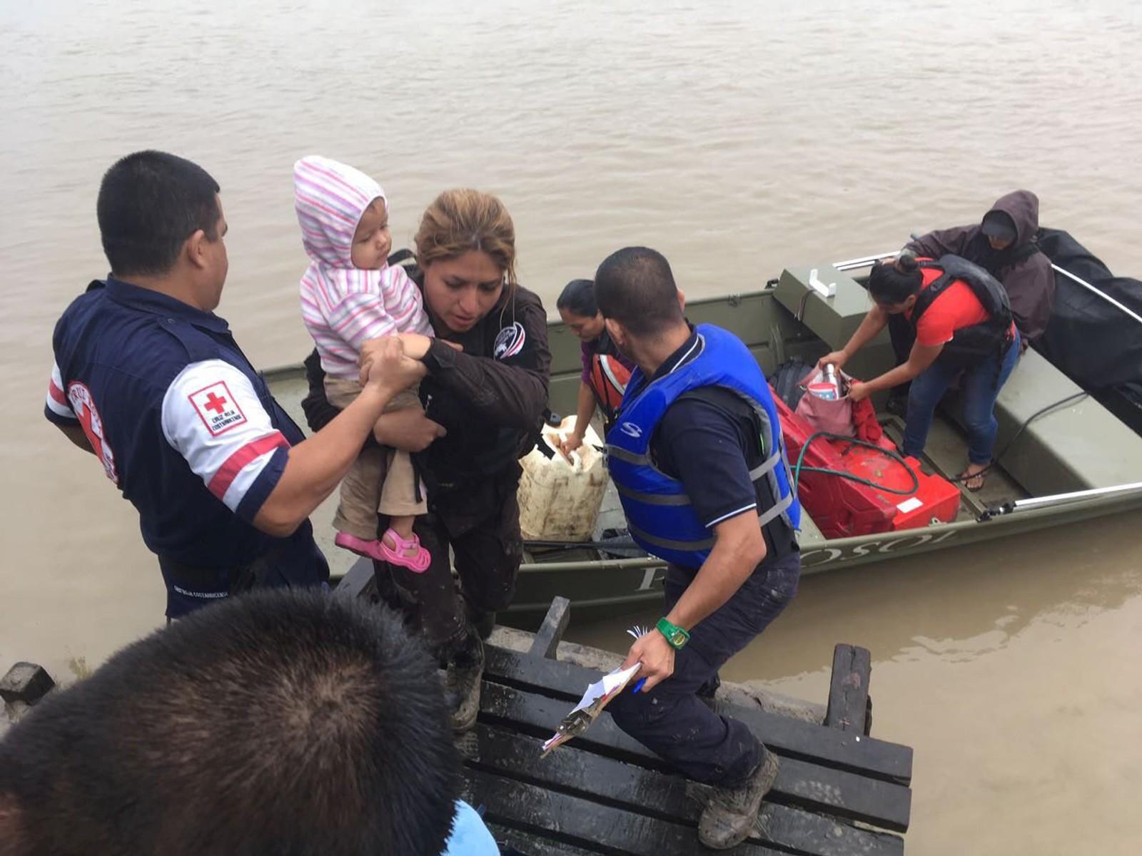 Personell frå Røde Kors hjelper familiar å evakuere i Barra de Colorado i Costa Rica.
