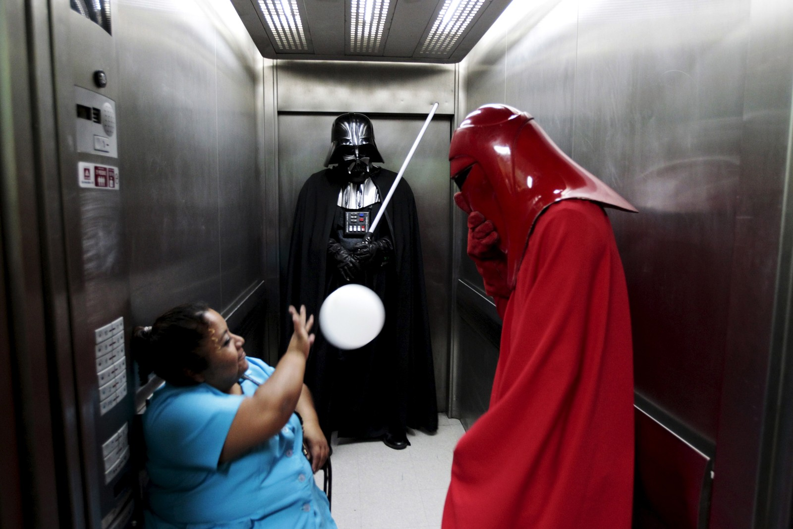 Heller ikke i El Salvador lot såkalte cosplayere sjansen gå fra seg til å spre litt av «kraften» i lokalmiljøet. Her får en heisoperatør testa Jedi-ferdighetene sine.