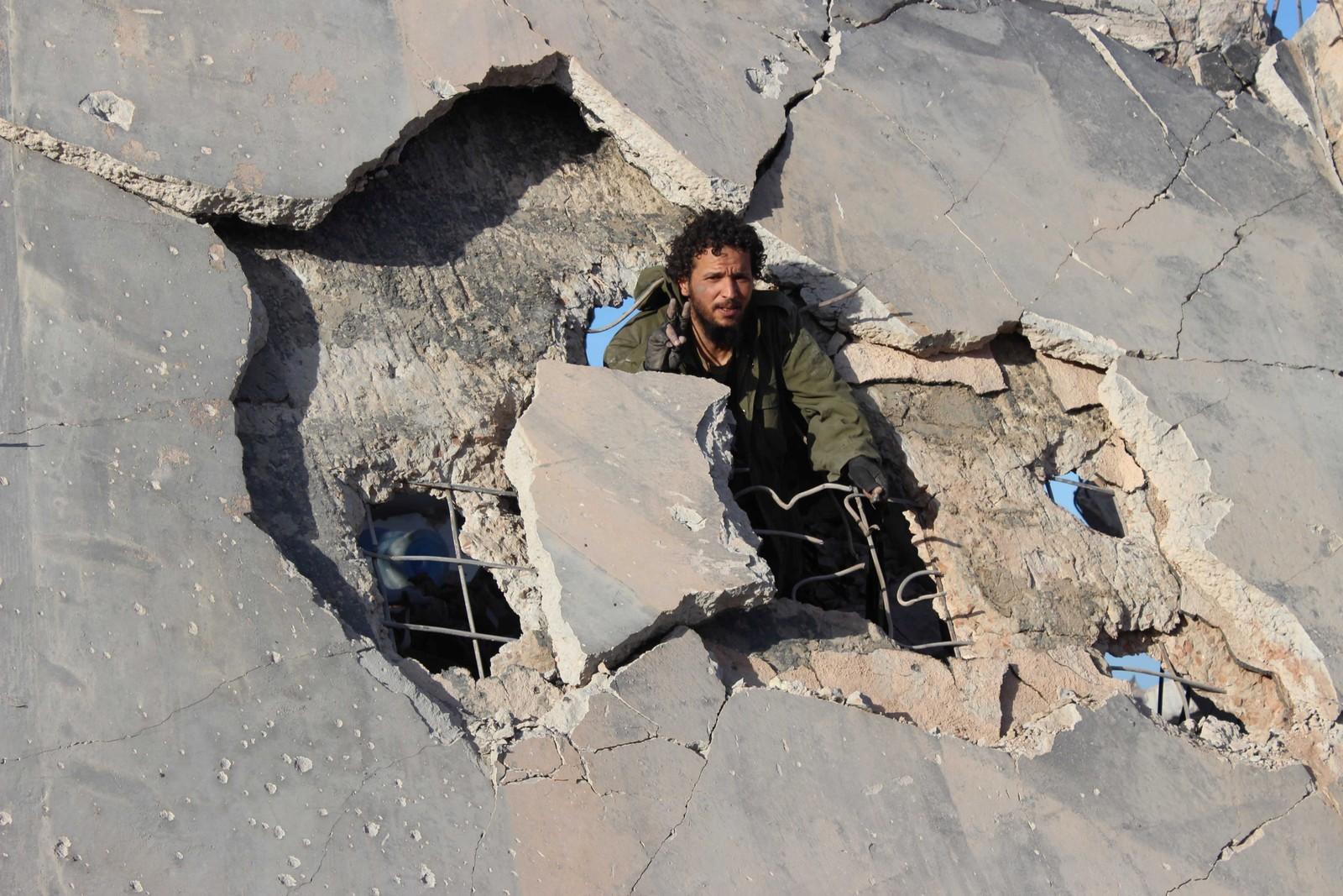 En libyisk soldat viser seierstegnet i den utbombede bygningen. De FN-støttede styrkene hevder å ha kontroll over den tidligere IS-bastionen Sirte.