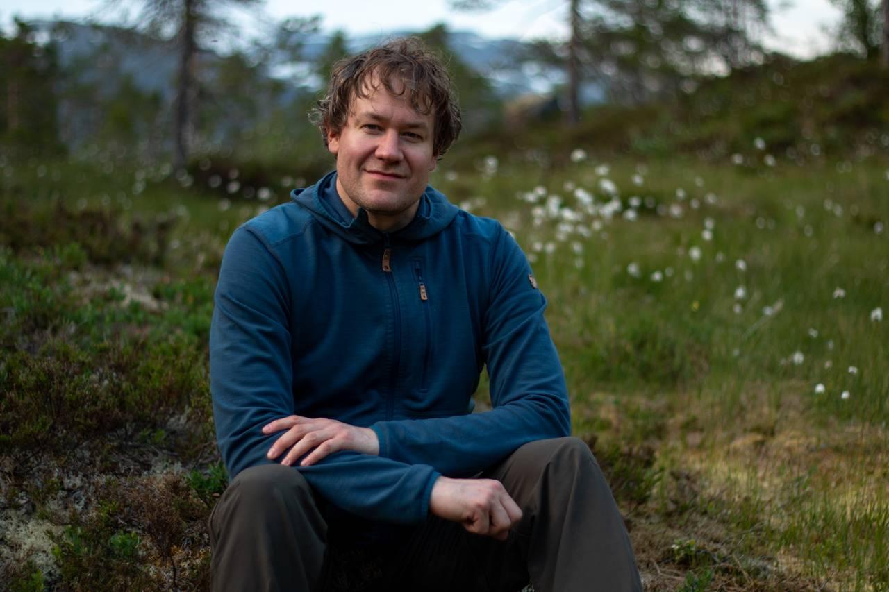 Portrettbilde av insektfotograf André som sitter i fjellyngen. Store fjell sees i bakgrunnen.