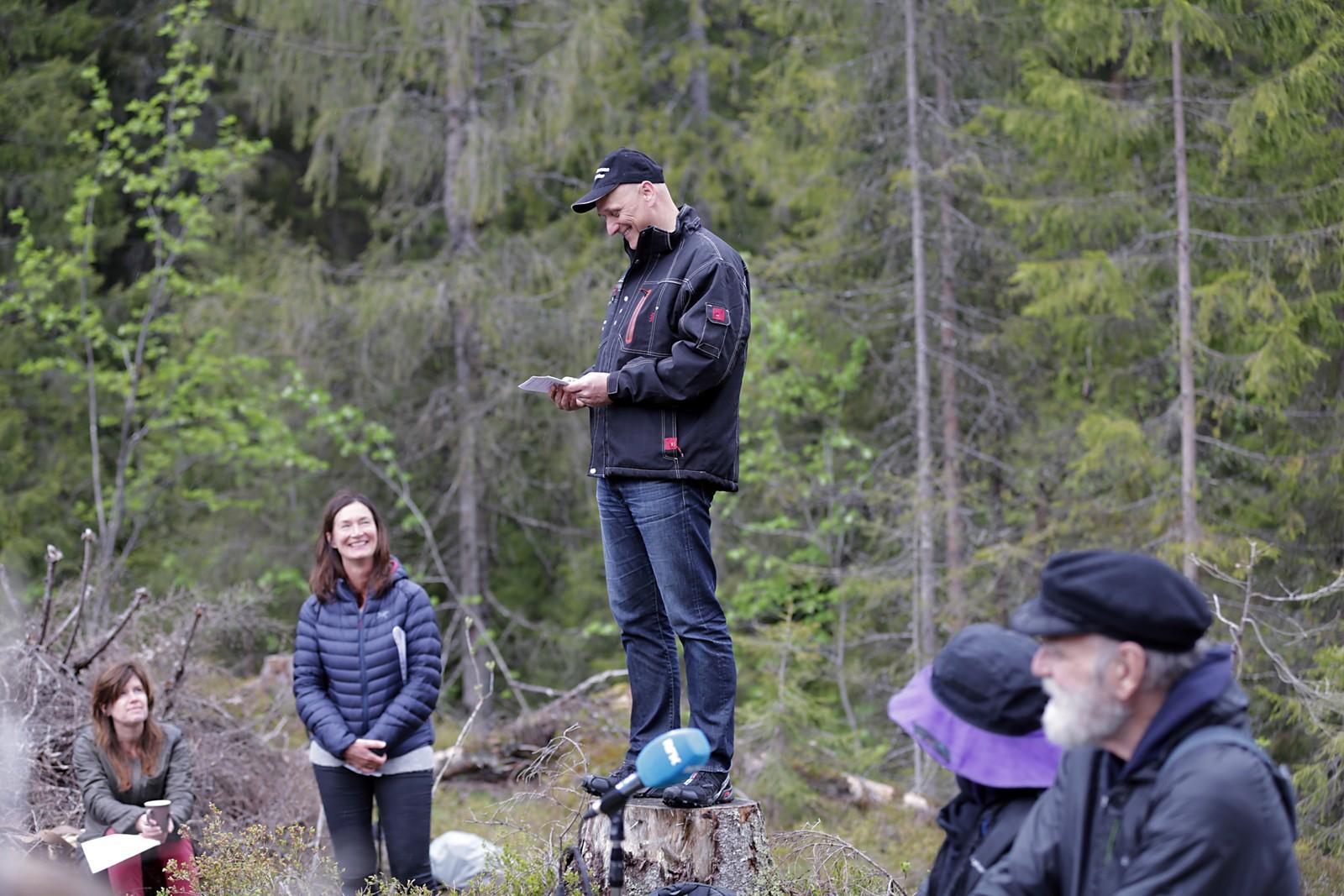 """Stubber i åpningen i skogen ble brukt som talestol. Skogvokteren forteller publikum at det for 125 år siden ble avgjort at skogen skulle være for Oslos innbyggere, til rekreasjon. """"That`s amazing"""", utbrytes det blant de utenlandske publikummerne som var med Atwood i skogen."""