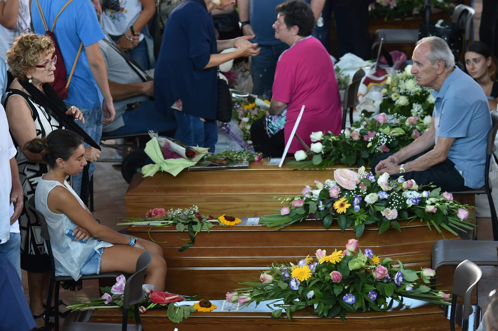 35 kister dekorerte med blomster og bilete stod inne i idrettshallen i Ascoli Piceno.