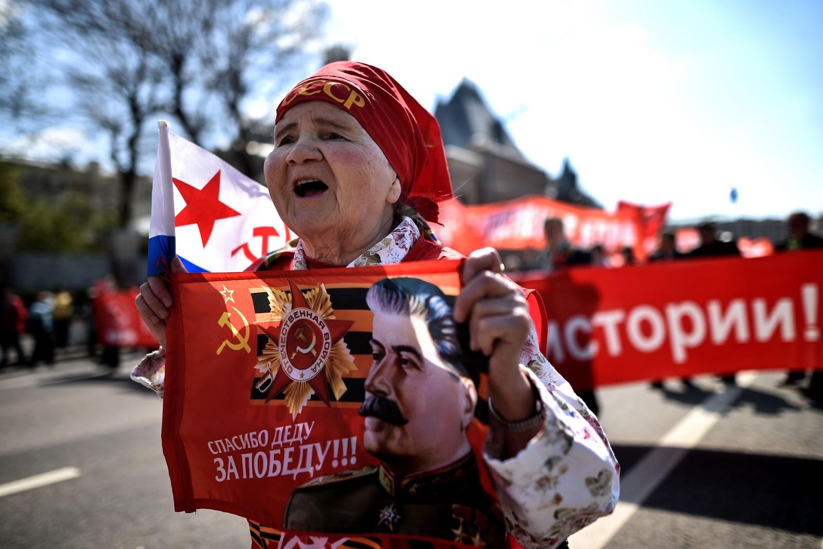 En kvinne, som er medlem av det russiske kommunistpartiet, bærer en banner med bilde av den avdøde sovjetiske lederen Joseph Stalin under en 1. mai-markering i Moskva søndag.