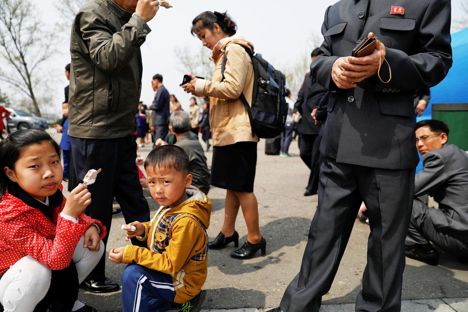 Barn med is utenfor en blomsterutstilling i Pyongyang.