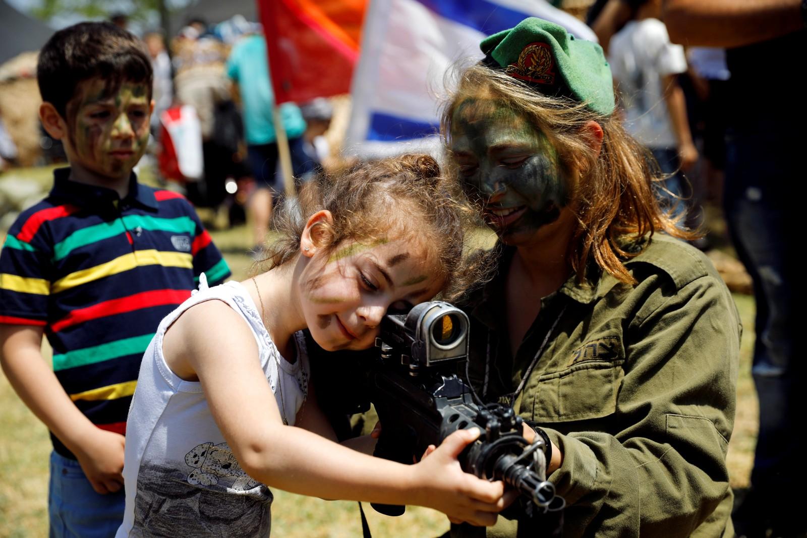 Og her får en liten jente prøve å holde et våpen. Det var den 69. gangen nasjonaldagen i Israel ble feiret. Dagen feires på forskjellige datoer hvert år.