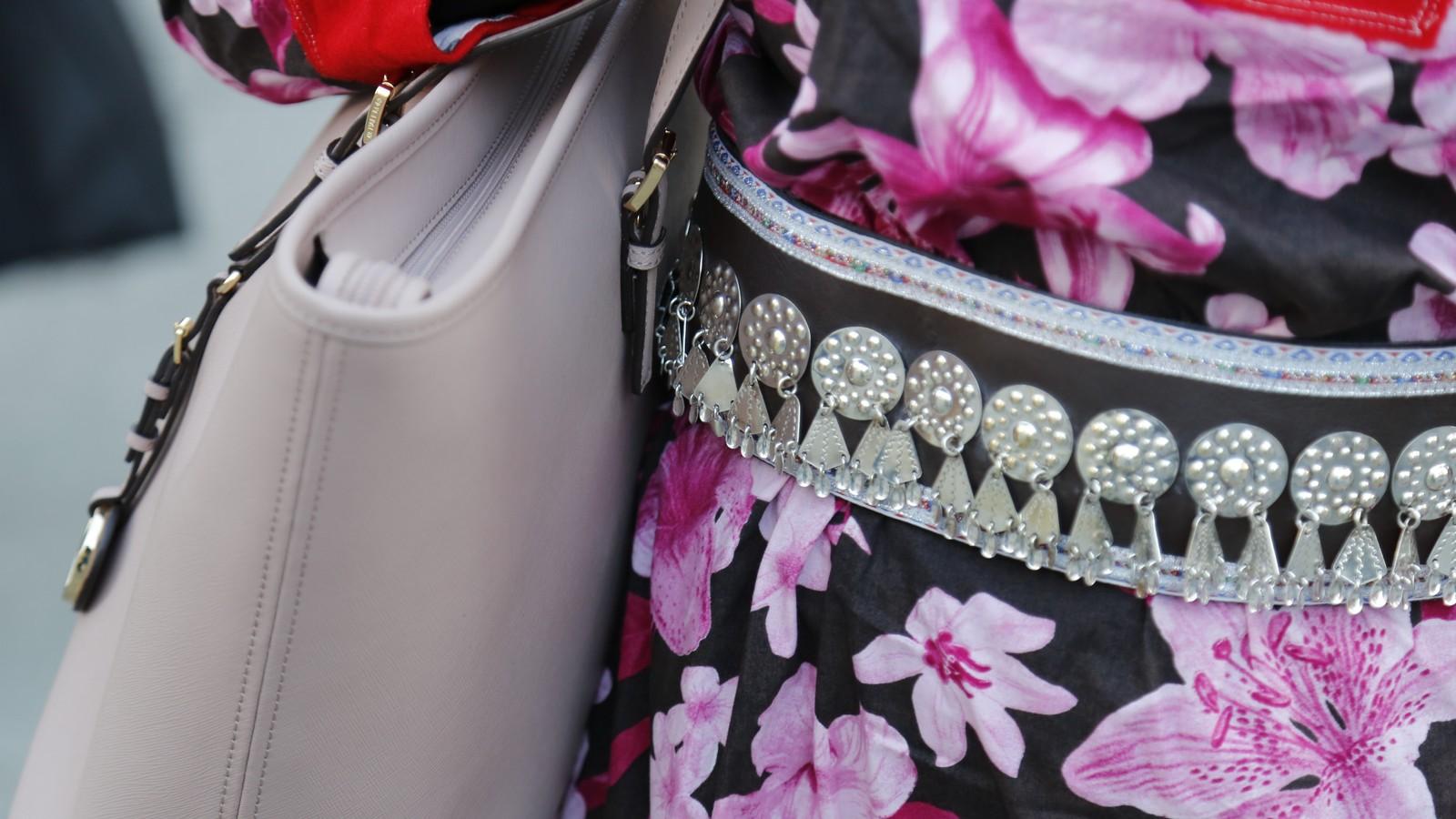 Nærbilde av storblomstrete samedrakt, belte med sølvknapper og en rosa veske. Man ser ikke kvinnen, kun kofta, beltet og veska.