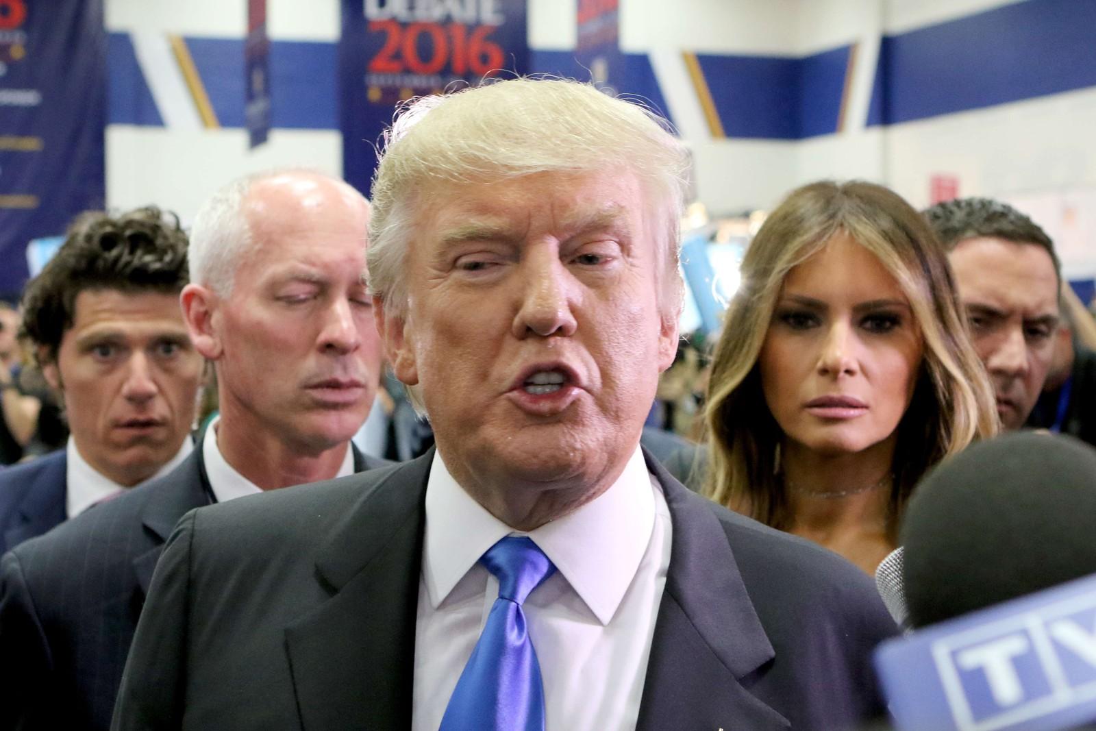 """Trump snakker med pressen i """"the spin room"""" etter debatten, med kona Melanie i bakgrunnen."""