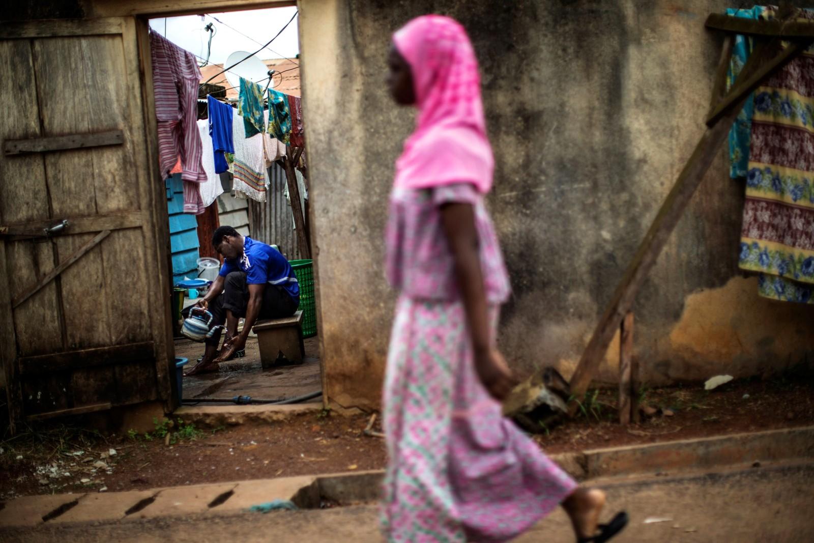 En mann går gjennom en rituell renselse mens en kvinne går forbi i Bitam, nord i Gabon den 5. september. Det har vært store uroligheter i landet etter valget den 27. august
