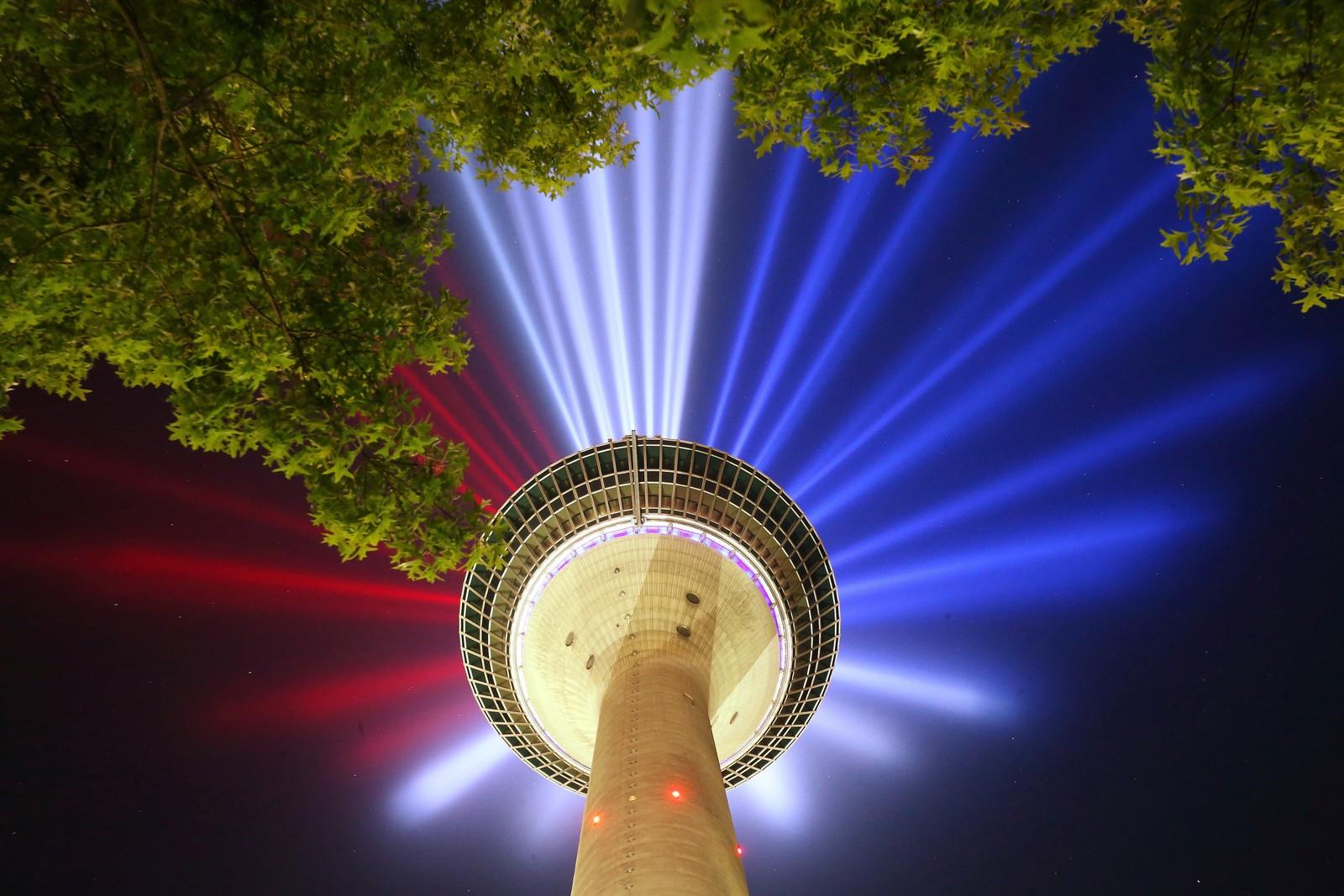 Det franske flaggets farger lyser ut fra tårnet Rheinturm i Düsseldorf i Tyskland. Tour de France starter nettopp her den 1. juli.