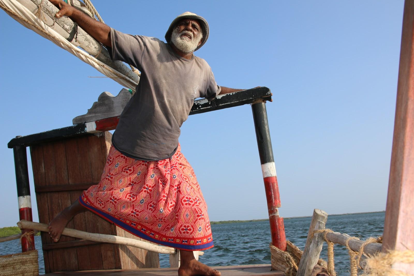 Kaptein Ali styrer dhowen med tærne på rorpinnen.
